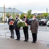 Składanie kwiatów pod tablicami na budynku urzędu masta