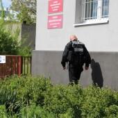 Policjant przed budynkiem szkoły - fot. Starostwo Powiatowe w Zgierzu